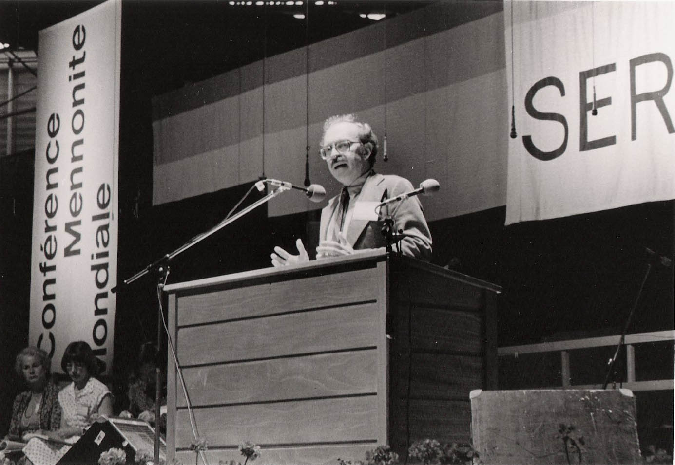 Ronald J. Sider stands behind a podium while making a speech