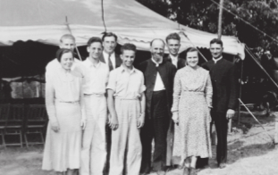 This photo, taken at the 1938 Iowa Camp Meeting near Knoxville, shows the members of the male quartet from Messiah Bible College, as well as the evangelist, the two other speakers, and the pianists/children's workers. Back row (left to right): Earl Musser (second tenor), J. W. Payne, Clair Hoffman (bass), and Bishop Ray I. Witter. Front row: Frances Smith, Hartman Landis (baritone), David Hoover (first tenor), Henry W. Landis, and Dorothy Witter.