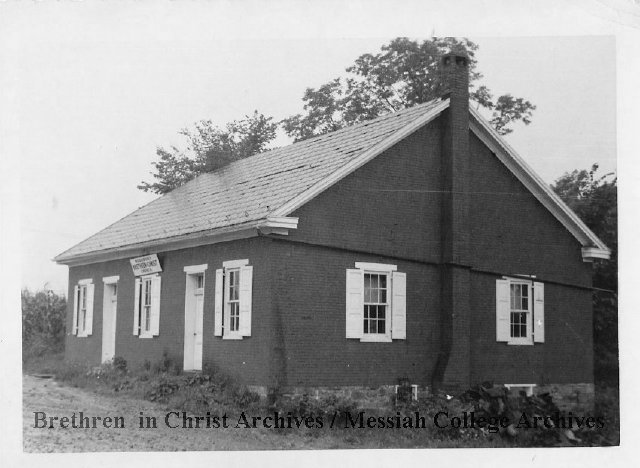 A black-and-white photo of an old brick building.