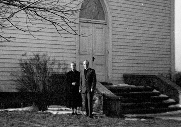 Pastor & Mrs Sider in front of bldg- larger