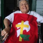 A woman sits in a chair with a hand-sewn version of the Brethren in Christ logo on her lap. The logo is a yellow cross on top of a white dove and a basin with a towel.